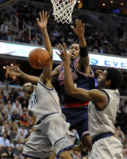 Memphis forward Ferrakohn Hall, center, competes with Georgetown's Otto Porter (22) and Hollis Thompson for a rebound during first half of an NCAA college basketball  game, Thursday, Dec. 22, 2011, in Washington. (AP Photo/Richard Lipski)