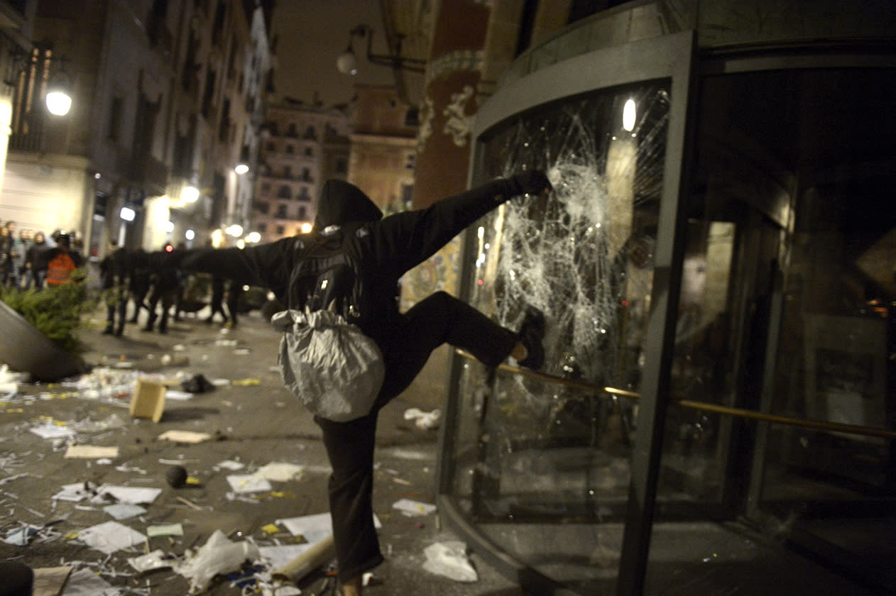"A demonstrator kicks the glass at the main entrance of ""Palau de la Musica"" during clashes following a demonstration during a general strike in Barcelona Spain."
