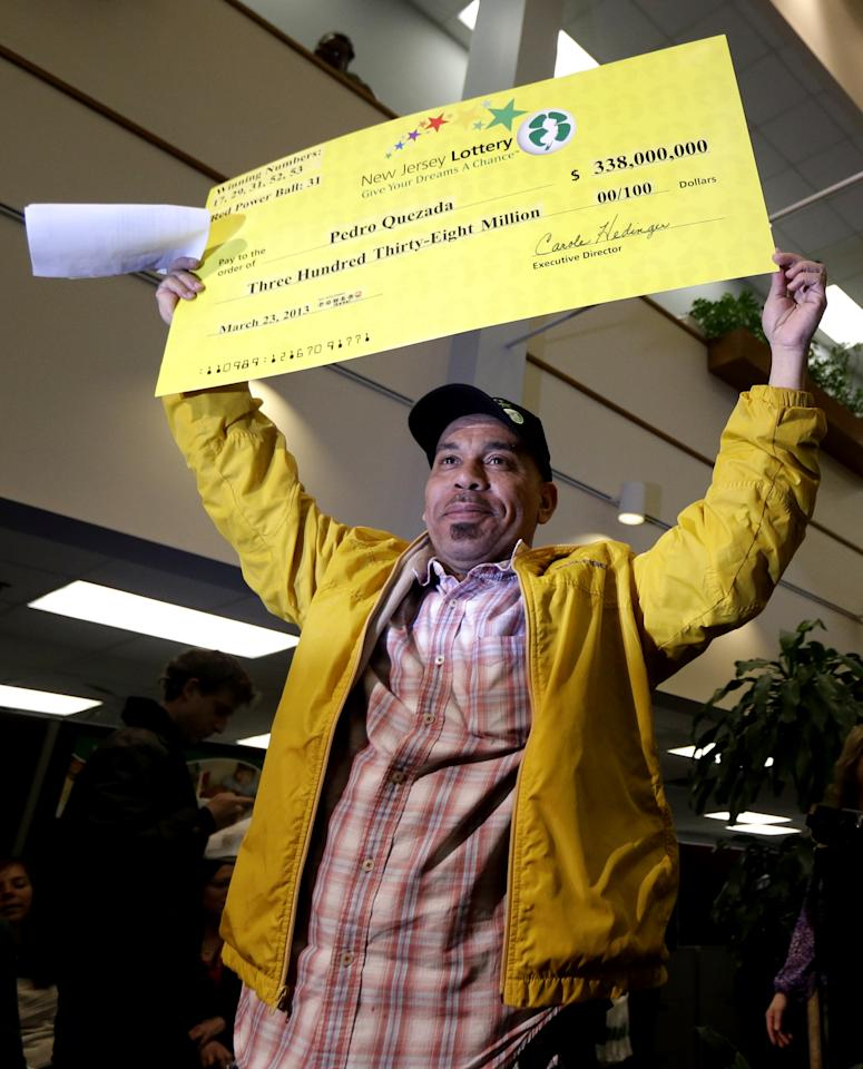 Pedro Quezada, the winner of the Powerball jackpot, holds up a promotional check during a news conference at the New Jersey Lottery headquarters, Tuesday, March 26, 2013, in Lawrenceville, N.J. Quezada , 44, won the $338 million jackpot with the winning ticket he purchased at Eagle Liquors store in Passaic, N.J. (AP Photo/Julio Cortez)