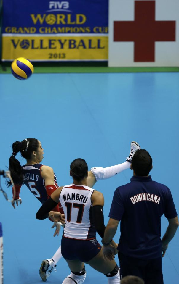 Brenda Castillo (5) of Dominican Republic kicks the ball against the U.S. as her team's coach Marcos Kwiek (R) and teammate Gina Altagracia Mambru Casilla look on during their FIVB Women's Volleyball Grand Champions Cup 2013 in Tokyo November 17, 2013. REUTERS/Toru Hanai (JAPAN - Tags: SPORT VOLLEYBALL)