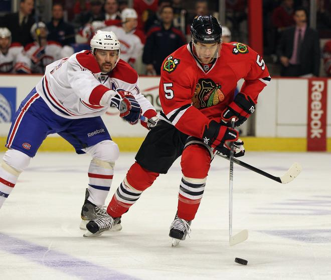 CHICAGO, IL - DECEMBER 21: Steve Montador #5 of the Chicago Blackhawks controls the puck under pressure from Tomas Piekanec #14 of the Montreal Canadiens at the United Center on December 21, 2011 in Chicago, Illinois. (Photo by Jonathan Daniel/Getty Images)