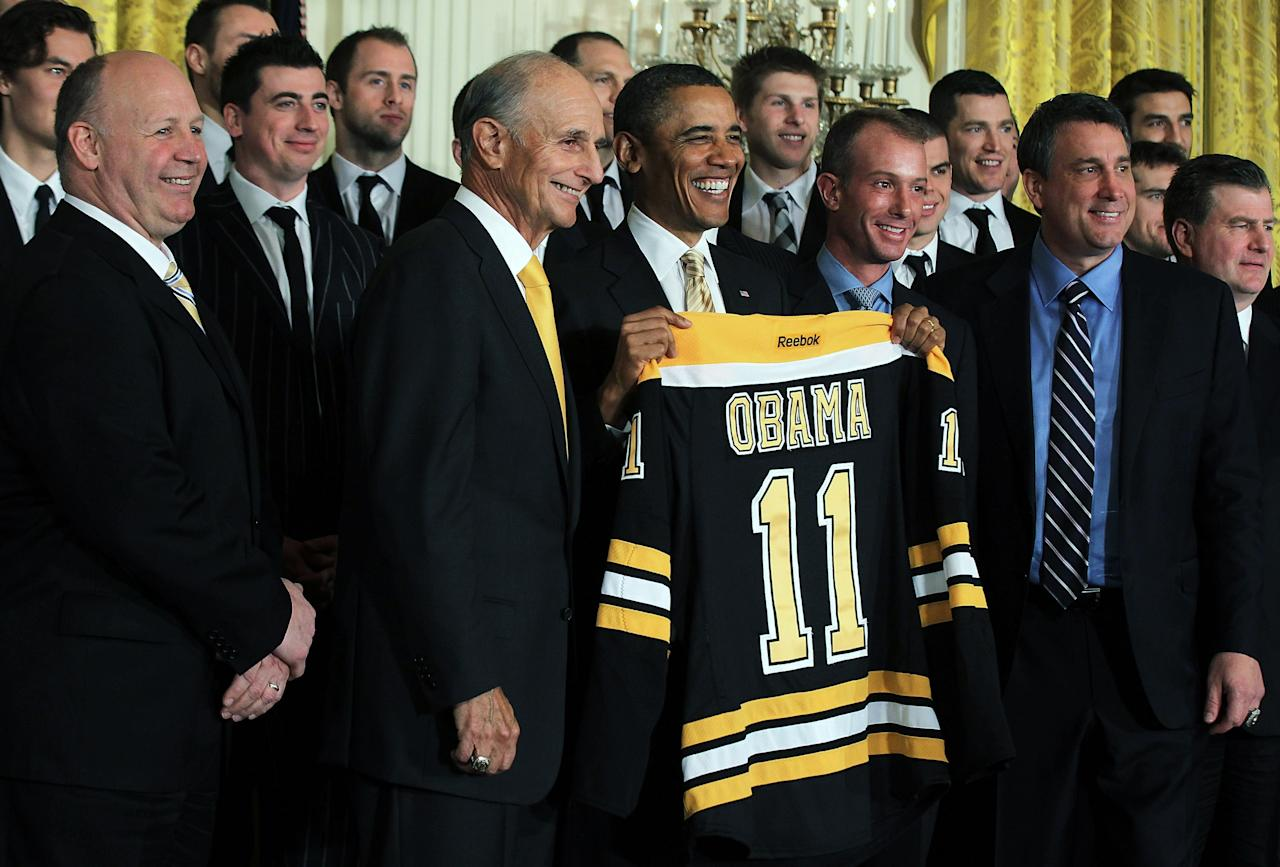 WASHINGTON, DC - JANUARY 23:  U.S. President Barack Obama (3rd L) poses for photos with members of the Boston Bruins (first row, L-R) head coach Claude Julien, team owner Jeremy Jacobs, Jacobs' son Charlie, team president of Cam Neely and assistant general manager Jim Benning after he was presented with a jersey by during a East Room event at the White House January 23, 2012 in Washington, DC. The six-time Stanley Cup champions were honored by the President for winning the 2011 Stanley Cup last June.  (Photo by Alex Wong/Getty Images)