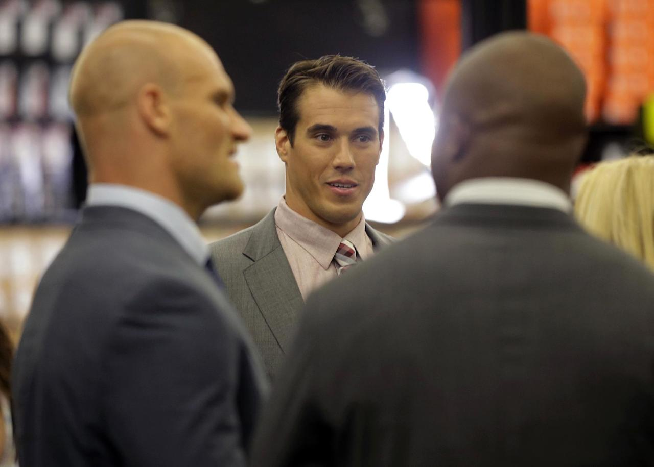 In this photo taken on Wednesday, June 18, 2014, former first-round draft pick, quarterback Brady Quinn, center, talks with fellow NFL football players Brady Poppinga, left, and Richard Johnson, right, at a sporting goods store during the NFL's Broadcast Boot Camp in Mount Laurel, N.J. Twenty-five current and former players participating in the NFL's Broadcast Boot Camp this week, are vying for broadcasting gigs. (AP Photo/Mel Evans)