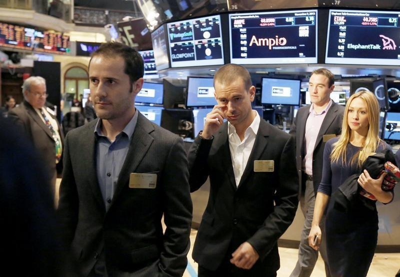 Twitter co-founders Williams and Dorsey walk together during the Twitter Inc. IPO on the floor of the New York Stock Exchange in New York