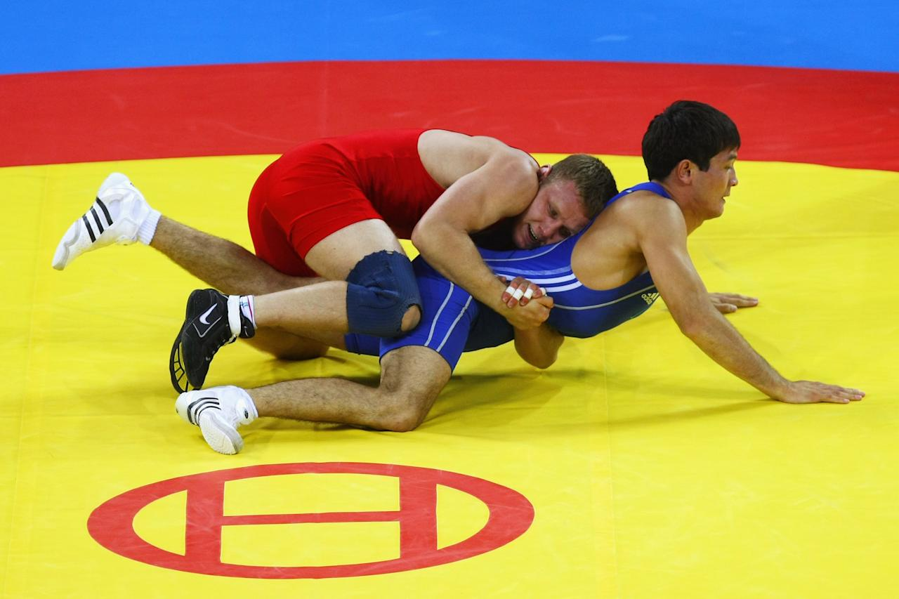 BEIJING - AUGUST 13:  Mikhail Siamionau (red) of Belarus grapples with Darkhan Bayakhmetov (blue) of Kazakhstan in the Men's Greco-Roman 66kg Bronze bout at the China Agriculture University Gymnasium during Day 5 of the Beijing 2008 Olympic Games on August 13, 2008 in Beijing, China.  (Photo by Clive Rose/Getty Images)