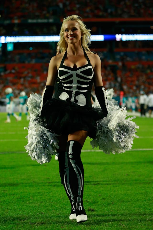 MIAMI GARDENS, FL - OCTOBER 31: A Miami Dolphins cheerleader looks on from the field during the game against the Cincinnati Bengals on Halloween night at Sun Life Stadium on October 31, 2013 in Miami Gardens, Florida. (Photo by Chris Trotman/Getty Images)