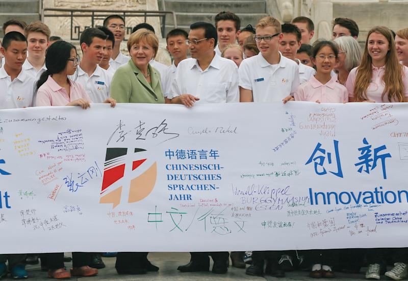 Angela Merkel (4th left) and Chinese Premier Li Keqiang (5th left) join Chinese and German highschool students holding a symbolic banner during a visit to the Temple of Heaven in Beijing on July 7, 2014