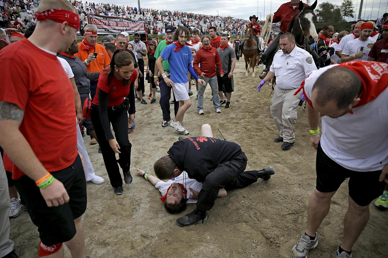 Bryant Knight, of Macon, Ga., is tended to by a medical official after being run over by a charging bull during the Great Bull Run at the Georgia International Horse Park, Saturday, Oct. 19, 2013, in Conyers, Ga. Knight was not seriously injured was able to walk off the track. The event, expected to attract 3,000 runners Saturday, is inspired by the annual running of the bulls in Pamplona, Spain and has future stops planned in Texas, Florida, California, Illinois and Pennsylvania. (AP Photo/David Goldman)