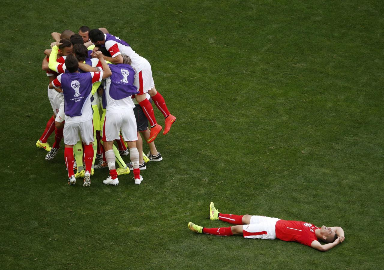 Switzerland players celebrate at the end of the 2014 World Cup Group E soccer match between Switzerland and Ecuador at the Brasilia national stadium in Brasilia, June 15, 2014. REUTERS/David Gray (BRAZIL - Tags: TPX IMAGES OF THE DAY SOCCER SPORT WORLD CUP)