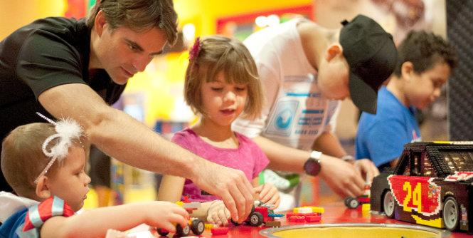 Jeff Gordon helps sisters Alaina Jones (left), 4, and Averie Jones, 6, build Lego cars during a recent visit with children battling cancer who have benefited from his foundation through Speedway Children's Charities-Texas Chapter. (Getty Images)