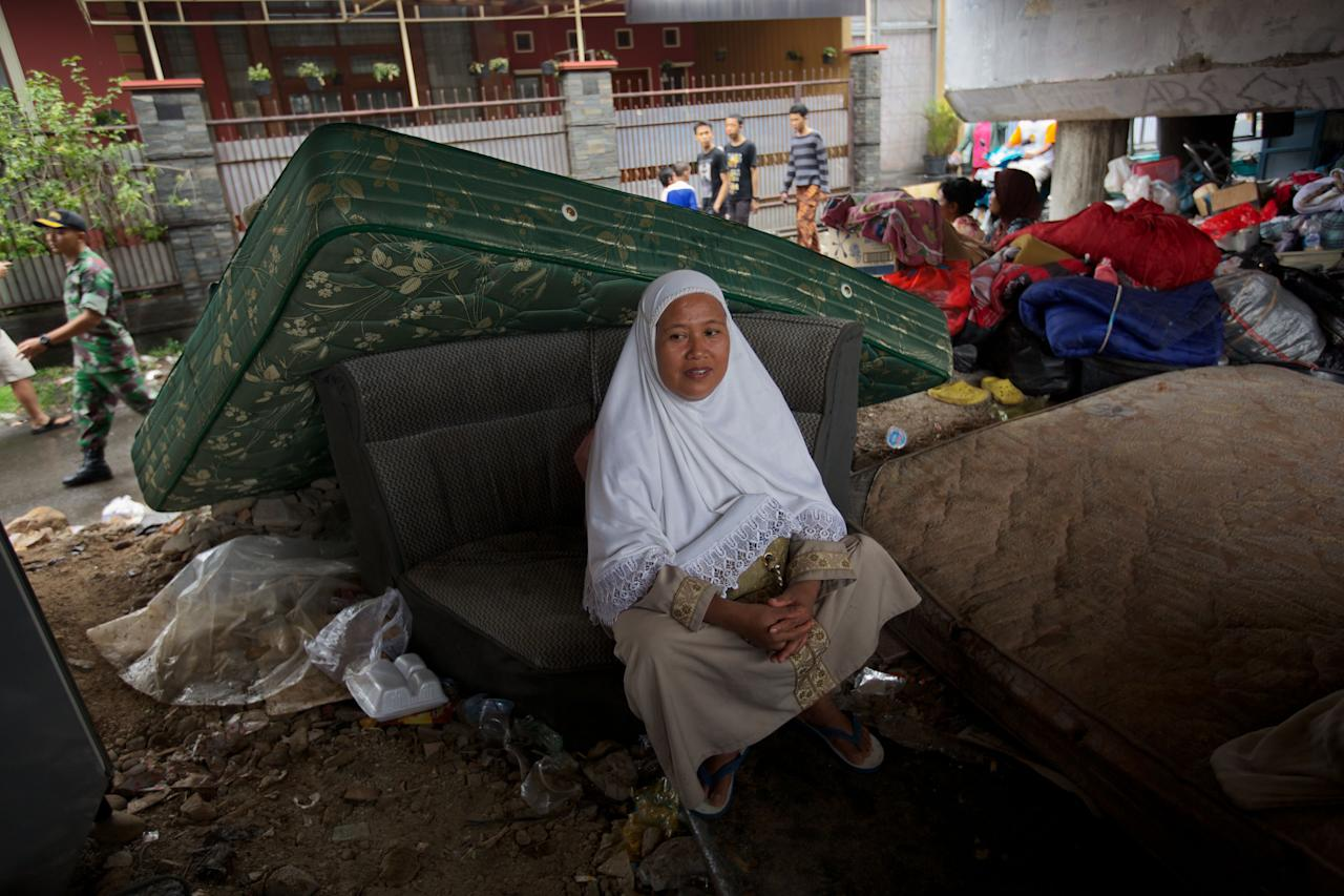 JAKARTA, INDONESIA - JANUARY 17:  People shelter from floodwaters amongst their belongings beneath an overpass, on January 17, 2013 in Jakarta, Indonesia.  Thousands of Indonesians were displaced and the capital was covered in many key areas in over a meter of water after days of heavy rain. (Photo by Ed Wray/Getty Images)
