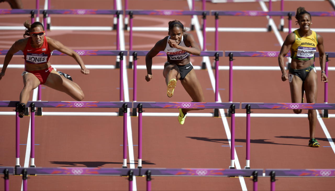United States' Lolo Jones, left, Canada's Phylicia George, center, and Jamaica's Brigitte Foster-Hylton compete in a women's 100-meter hurdles heat during the athletics in the Olympic Stadium at the 2012 Summer Olympics, London, Monday, Aug. 6, 2012. (AP Photo/Martin Meissner)