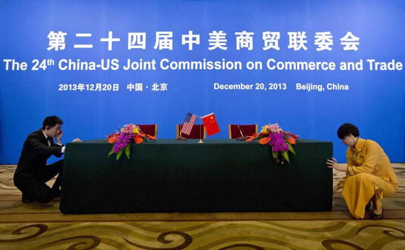An usher and a hostess prepare a table for a signing ceremony after a meeting of the 24th China-U.S. Joint Commission on Commerce and Trade in Beijing