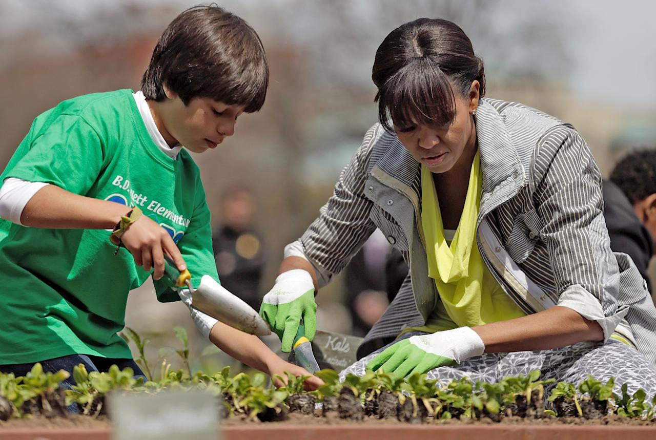 """WASHINGTON, DC - APRIL 04:  U.S. first lady Michelle Obama plants the White House Kitchen Garden with fifth grader Emilo Vega of Florida on the South Lawn of the White House April 4, 2013 in Washington, DC. For the fifth time, the first lady invited students from """"schools that have made exceptional improvements to school lunches from Florida, Massachusetts, Tennessee and Vermont to help her plant the garden.  (Photo by Win McNamee/Getty Images)"""