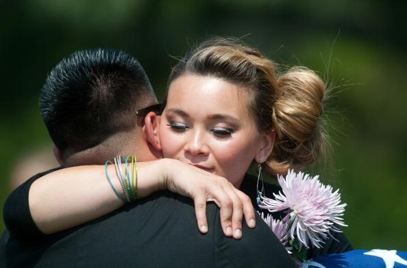 Chantel Blunk, wife of Aurora shooting victim Jonathan Blunk, hugs a guest following her husband's funeral August 3, 2012 in Reno, Nevada. Blunk, a U.S. Navy veteran, was buried with full military honors after being killed by alleged shooter James Holmes in the Aurora, Colorado movie theater shooting on July 20. (Photo by David Calvert/Getty Images)