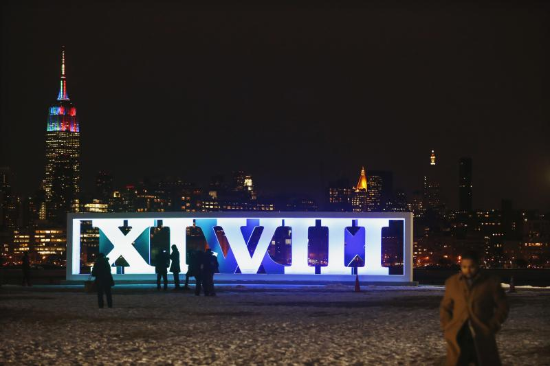New York skyline and Empire State Building are seen in distance as people take pictures near roman numerals for NFL Super Bowl XLVIII football game in Hoboken