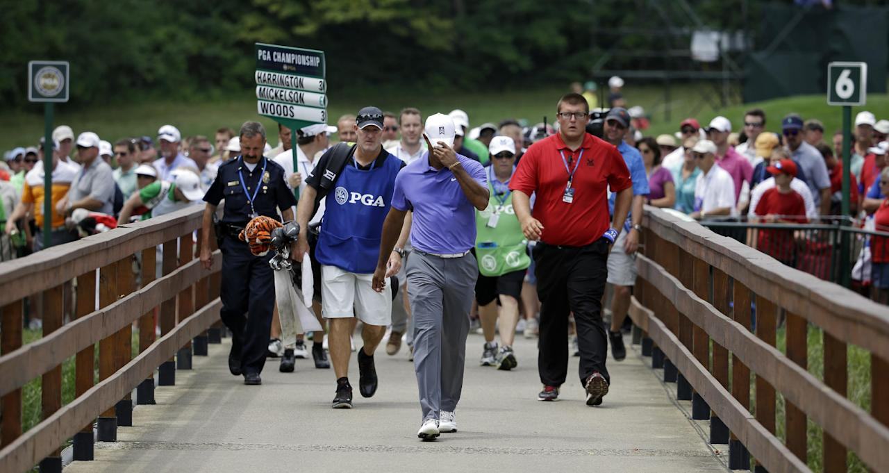 Tiger Woods hangs is head as he walks across the bridge to the seventh fairway during the first round of the PGA Championship golf tournament at Valhalla Golf Club on Thursday, Aug. 7, 2014, in Louisville, Ky. (AP Photo/John Locher)