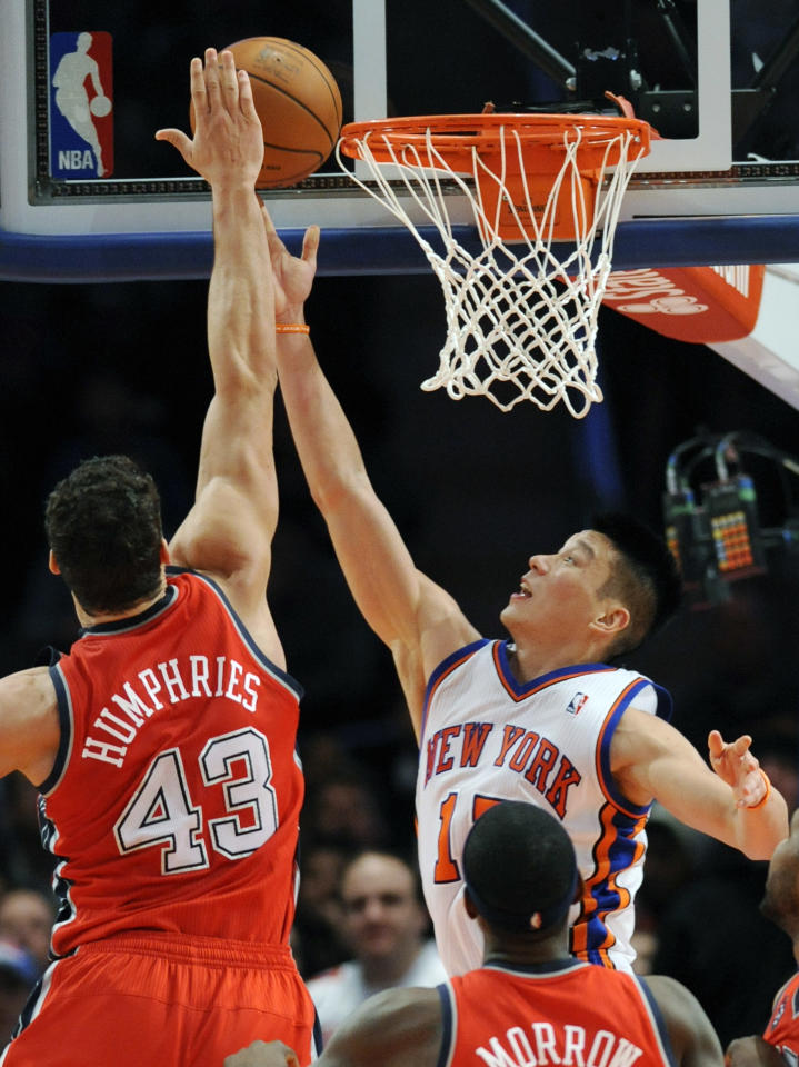 New York Knicks guard Jeremy Lin, top right, puts up a shot as New Jersey Nets forward Kris Humphries defends during the fourth quarter of an NBA basketball game on Saturday, Feb. 4, 2012, at Madison Square Garden in New York. Lin led all scorers with 25 points as the Knicks defeated the Nets 99-92. (AP Photo/Bill Kostroun)