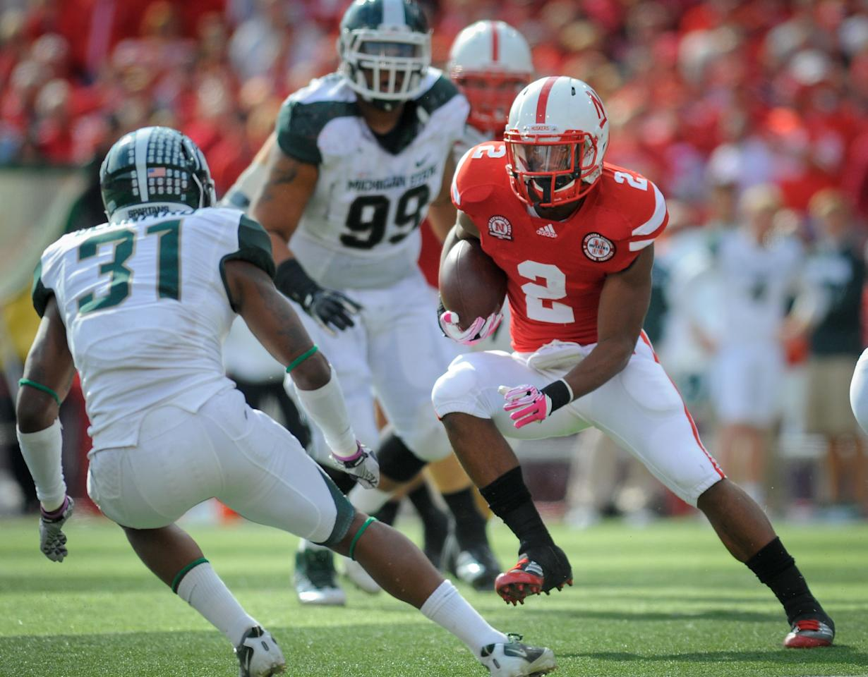 LINCOLN, NE - OCTOBER 29: Running back Aaron Green #2 of the Nebraska Cornhuskers tries to avoid cornerback Darqueze Dennard #31 of the Michigan State Spartans during their game at Memorial Stadium October 29, 2011 in Lincoln, Nebraska. (Photo by Eric Francis/Getty Images)
