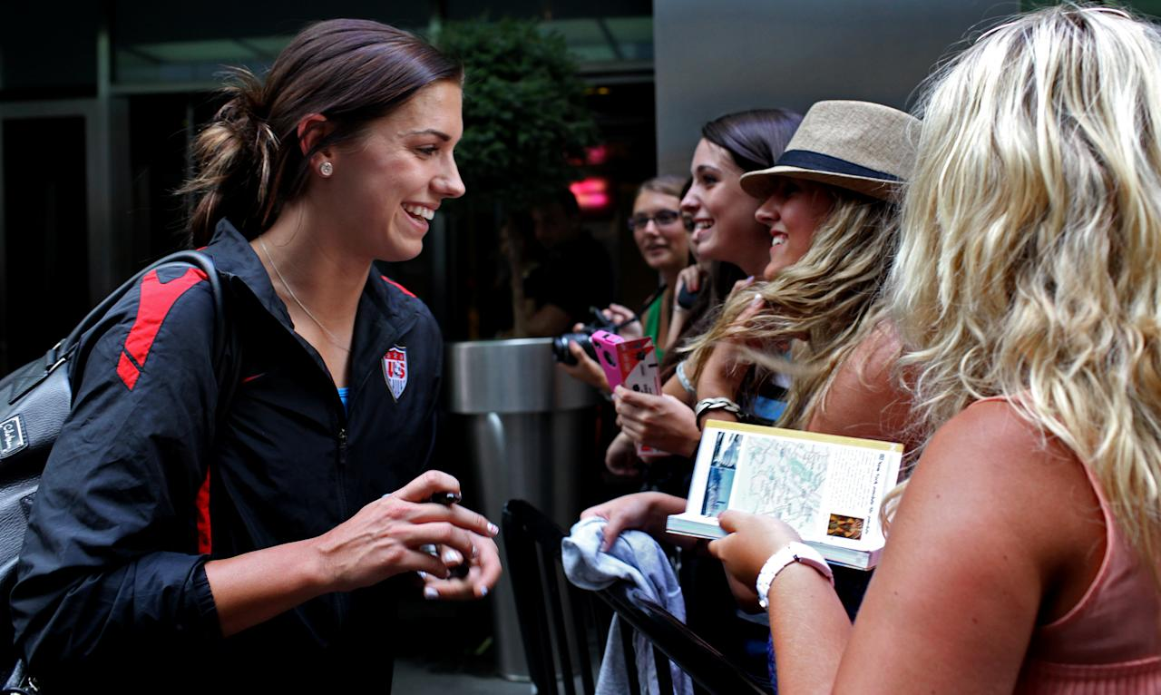 Alex Morgan greets fans after she and other members of the U.S. soccer team arrived in New York's Times Square on Monday, July 18, 2011, the day after the team's loss to Japan in the Women's World Cup final in Germany. (AP Photo/Craig Ruttle)