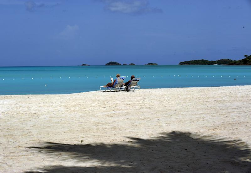 File photo of a couple sunbathing on a beach in St John's, Antigua and Barbuda