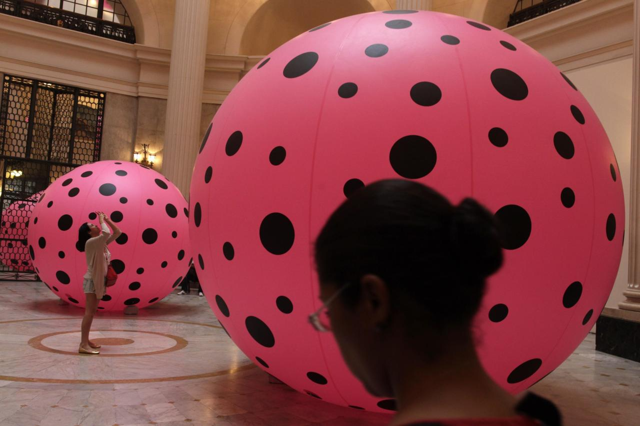 "A visitor takes photos of inflatable plastic balloons, part of the ""Dots Obsession"" exhibition created by Japanese pop artist Yayoi Kusama in Rio de Janeiro October 17, 2013. REUTERS/Pilar Olivares(BRAZIL - Tags: SOCIETY)"