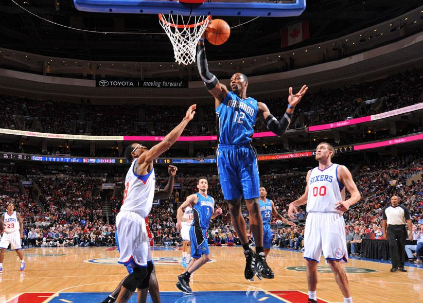 PHILADELPHIA, PA - APRIL 7:  Dwight Howard #12 of the Orlando Magic grabs a rebound over Andre Iguodala #9 and Spencer Hawes #00 of the Philadelphia 76ers on April 7, 2012 at the Wells Fargo Center in Philadelphia, Pennsylvania.    NOTE TO USER: User expressly acknowledges and agrees that, by downloading and/or using this Photograph, user is consenting to the terms and conditions of the Getty Images License Agreement. Mandatory Copyright Notice: Copyright 2012 NBAE
