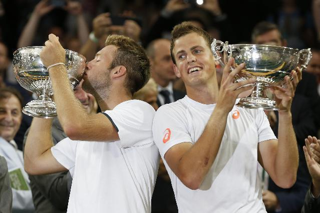 Vasek Pospisil of Canada, right, and Jack Sock of the U.S hold their trophies after defeating Bob Bryan and Mike Bryan of the U.S in the men's doubles final at the All England Lawn Tennis Championships in Wimbledon, London, Saturday July 5, 2014