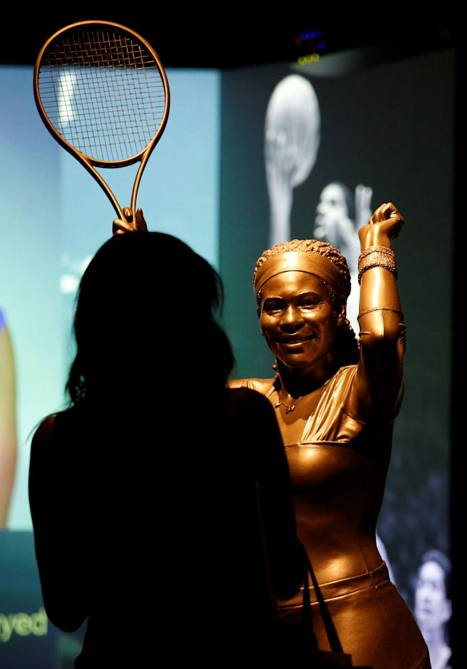 A woman stands before a statue of tennis great Serena Williams during a media preview day at the National Museum of African American History and Culture on the National Mall in Washington September 14, 2016. The museum will open to the public on September 24. REUTERS/Kevin Lamarque      FOR EDITORIAL USE ONLY. NO RESALES. NO ARCHIVES.
