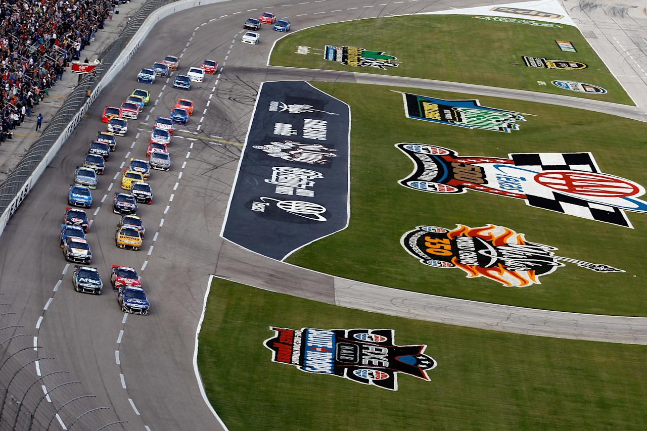 FORT WORTH, TX - NOVEMBER 06:  Matt Kenseth, driver of the #17 Crown Royal Ford, and Carl Edwards, driver of the #99 Aflac Ford, leads the field to a restart in the NASCAR Sprint Cup Series AAA Texas 500 at Texas Motor Speedway on November 6, 2011 in Fort Worth, Texas.  (Photo by Todd Warshaw/Getty Images for NASCAR)
