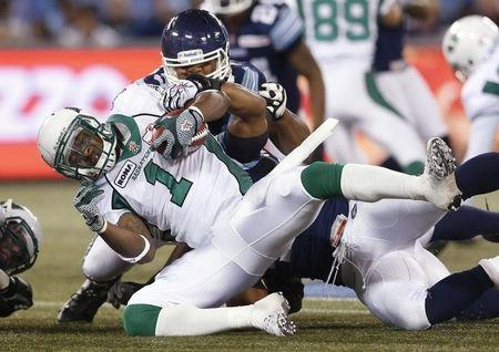 Saskatchewan Roughriders' Sheets runs the ball against Toronto Argonauts' Armstead during their CFL football game in Toronto