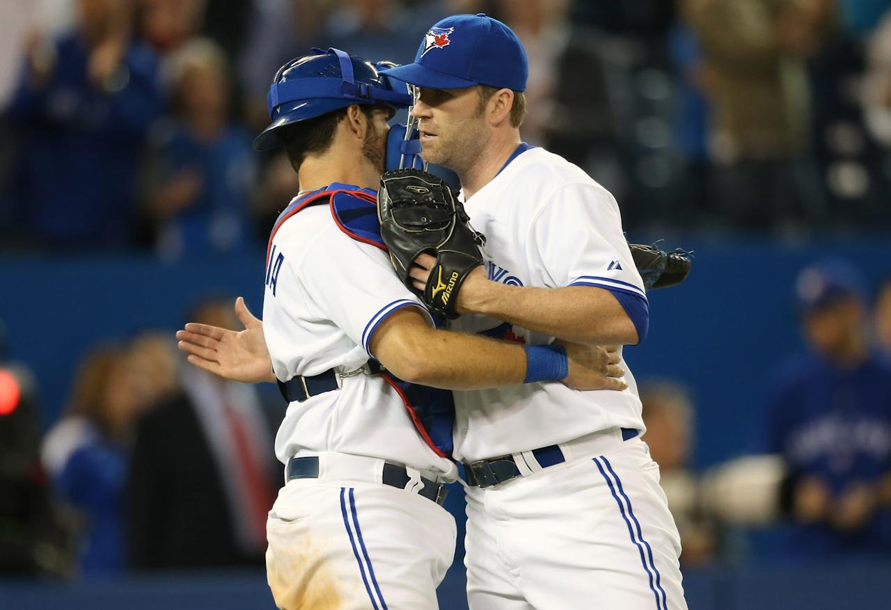 TORONTO, CANADA - JUNE 19: J.P. Arencibia #9 of the Toronto Blue Jays celebrates their win with Casey Janssen #44 during MLB game action against the Colorado Rockies on June 19, 2013 at Rogers Centre in Toronto, Ontario, Canada. (Photo by Tom Szczerbowski/Getty Images)