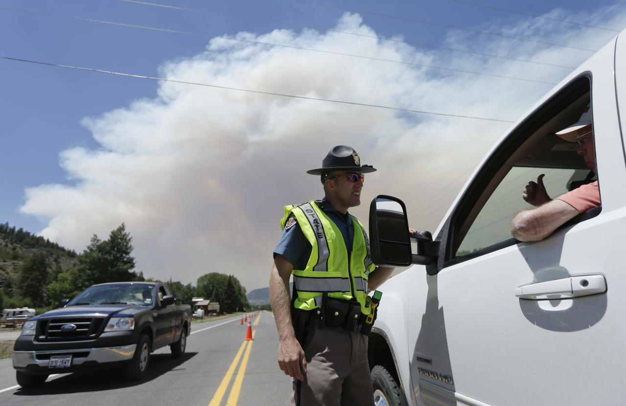 Colorado State Patrol officer Jessie Bartunek talks to a motorist as he stands at a checkpoint near South Fork, Colo., Sunday, June 23, 2013. A large wildfire near a popular summer retreat in southern Colorado continues to be driven by winds and fueled by dead trees in a drought-stricken area, authorities said Sunday. (AP Photo/Gregory Bull)