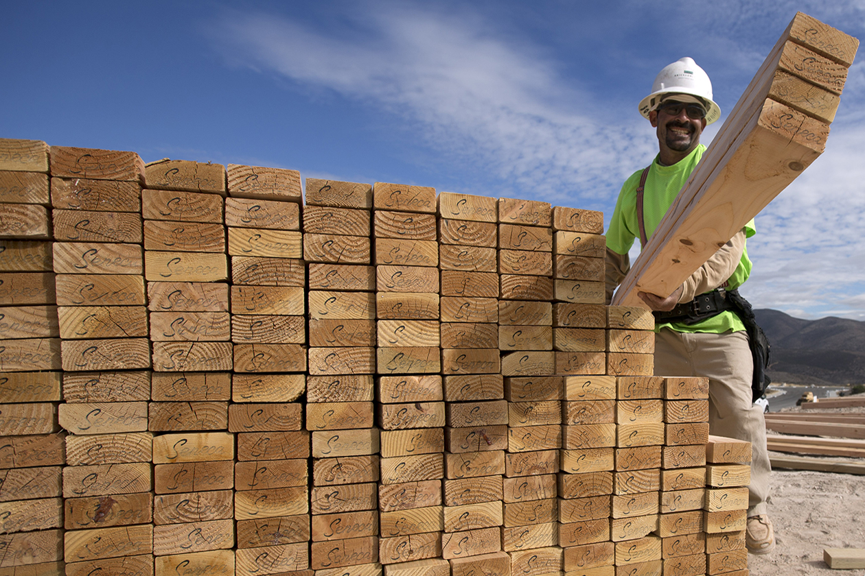 A construction worker carries lumber as he works on a house frame.