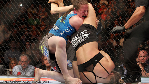 Ronda Rousey works Sarah Kaufman for her armbar on Saturday. (Tracy Lee for Y! Sports)