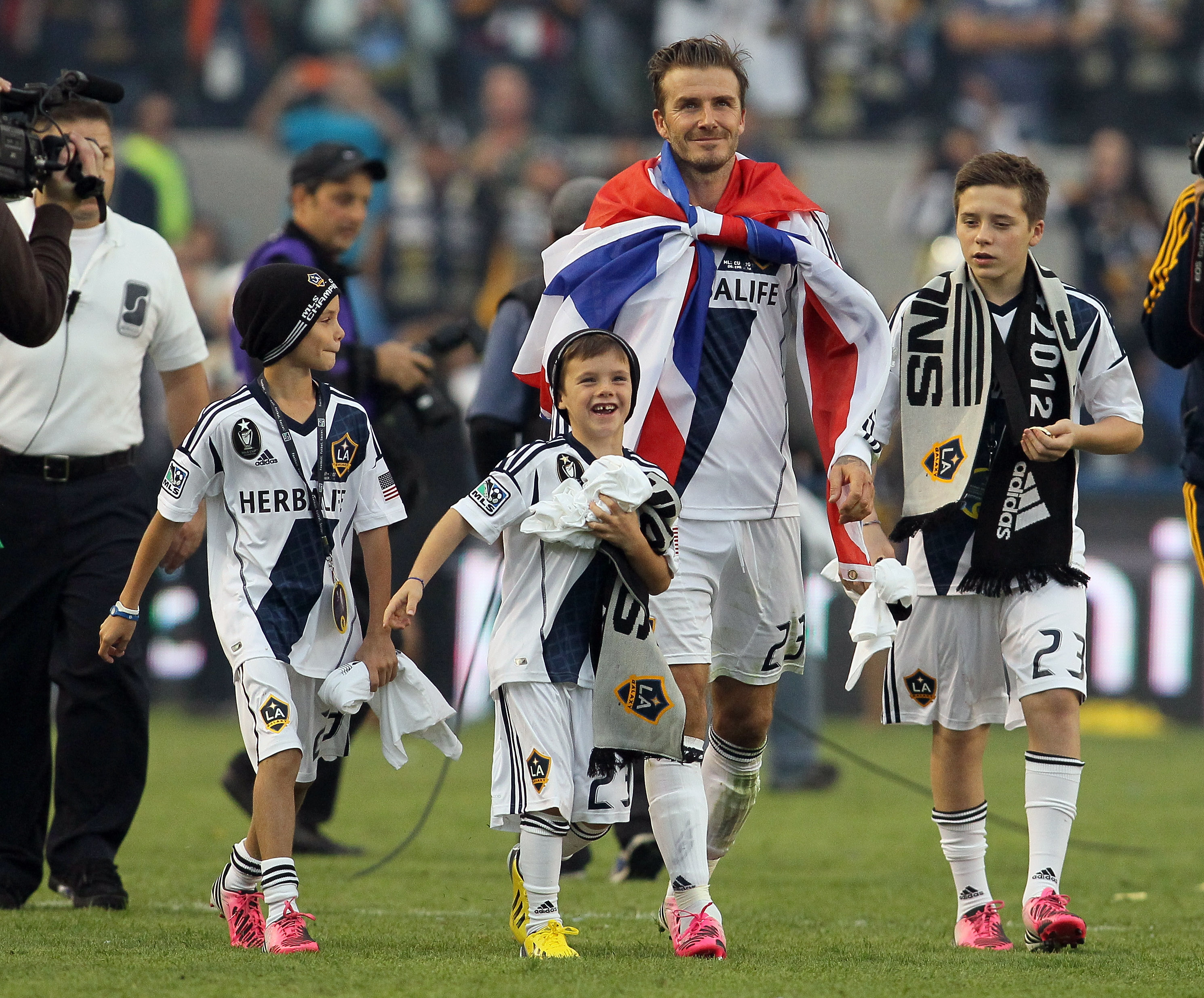 David Beckham walks off the field with his sons. (Getty)
