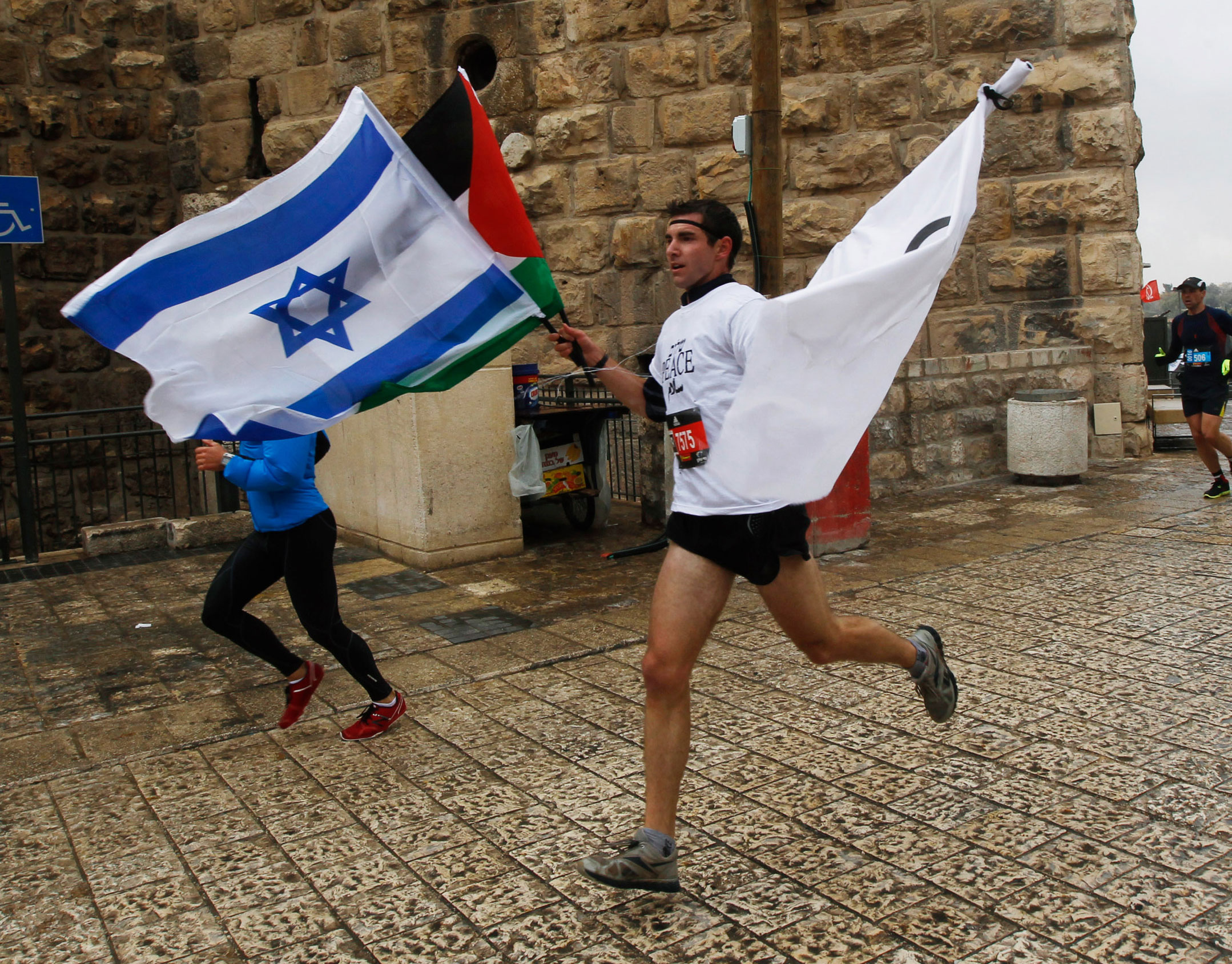 A runner holds an Israeli and Palestinian flag as he takes part in the Jerusalem Marathon. (Getty Images)