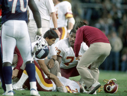 Joe Theismann receives attention after receiving the career-ending injury against the Giants. (Getty)