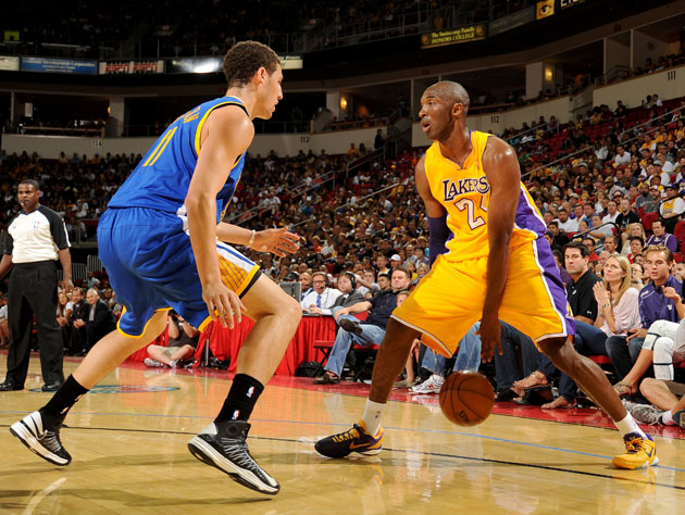 Kobe Bryant wears two different shoes during an exhibition game…
