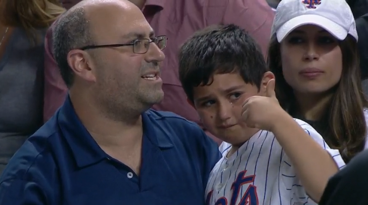 A Mets fan gives a thumbs up after being hit on the arm with a foul ball. (MLB.TV)