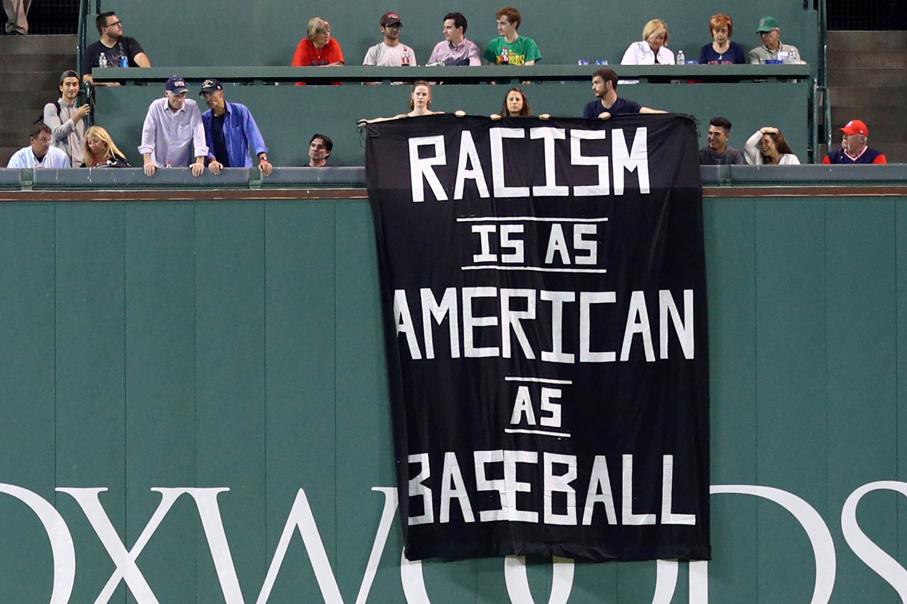 Protesters hang banner at Fenway Park that says 'Racism is as American as baseball'