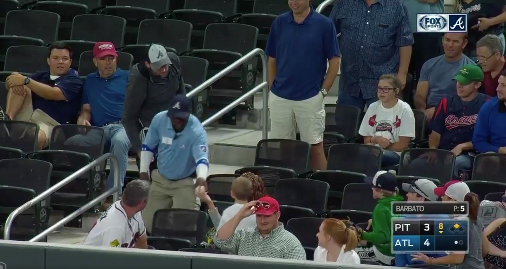 A Braves security guard takes a ball from a kid at Wednesday night's game. (MLB.tv)