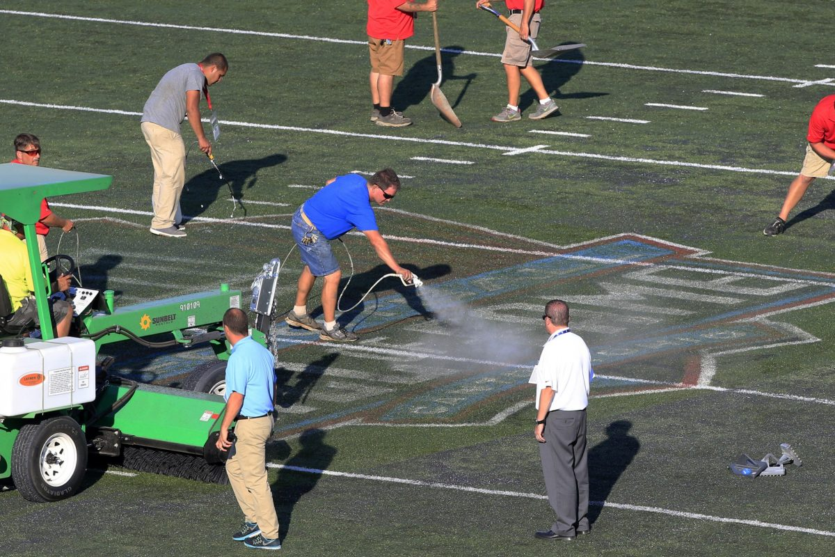 Workers tend to the field at Hall of Fame Stadium (AP)