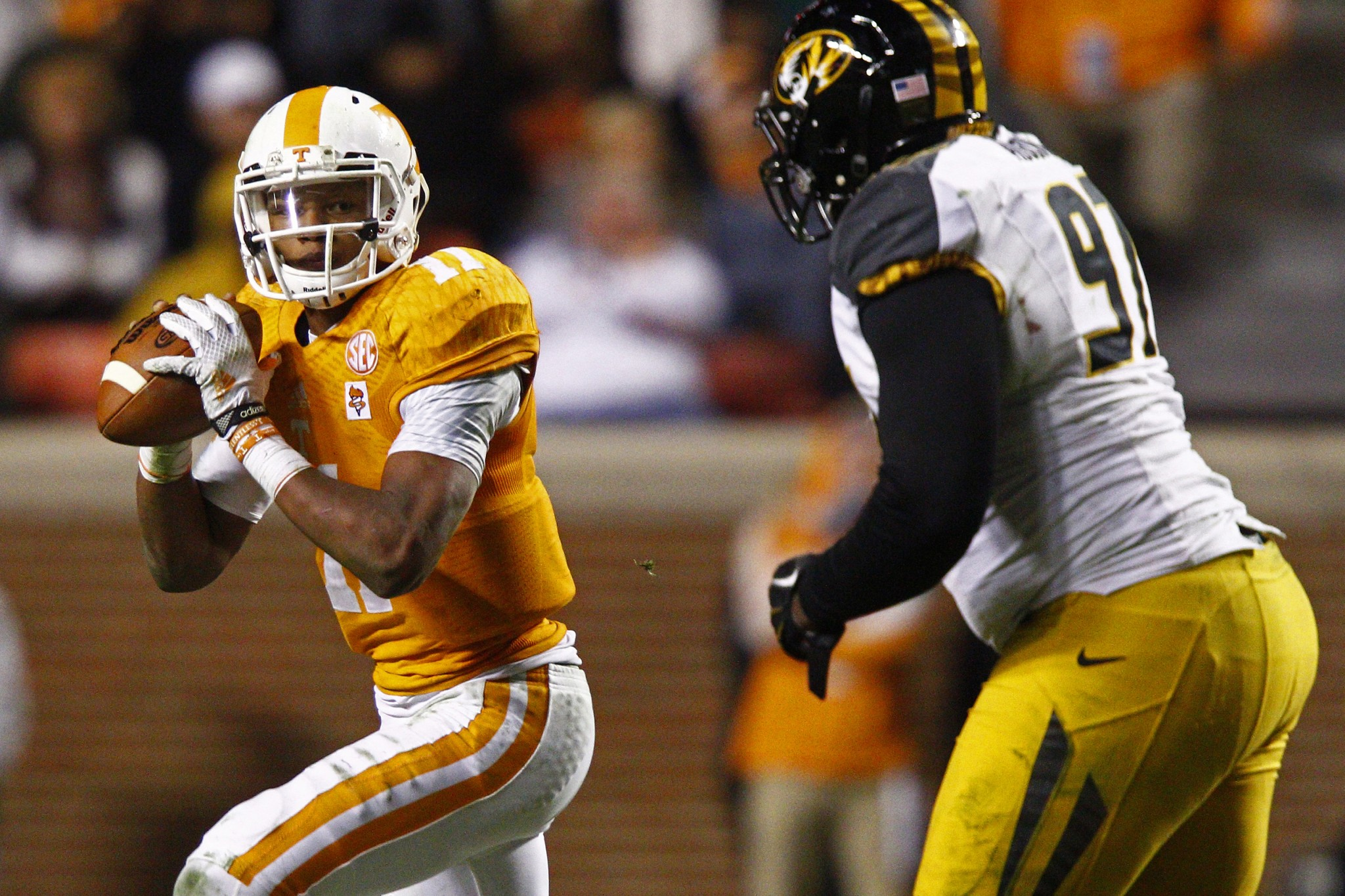 Tennessee quarterback Joshua Dobbs (11) looks for a receiver as he's pressured by Missouri defensive lineman Josh Augusta (97) in the second half of an NCAA college football game Saturday, Nov. 22, 2014 in Knoxville, Tenn. Missouri won 29-21. (AP Photo/Wade Payne)