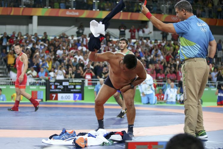 The coach of Mandakhnaran Ganzorig (MGL) of Mongolia takes off his clothes as he protests after the match against Ikhtiyor Navruzov (UZB) of Uzbekistan. (Reuters)