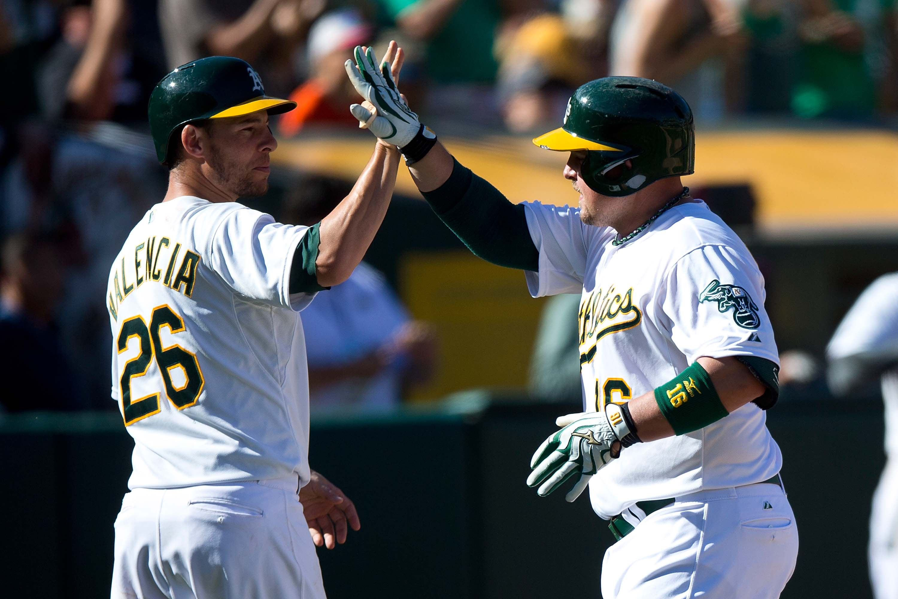 Billy Butler and Danny Valencia share a high-five and not fists during a recent game. (Getty Images/Jason O. Watson)