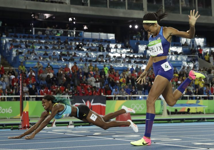 Shaunae Miller (L) is shown diving across the finish line ahead of Allyson Felix. (AP)