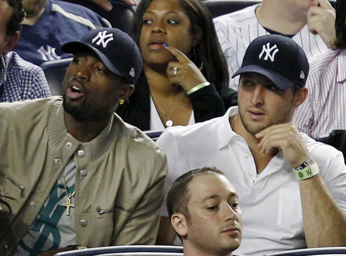 Tim Tebow, right, with Dwyane Wade at a 2012 New York Yankees game (AP)