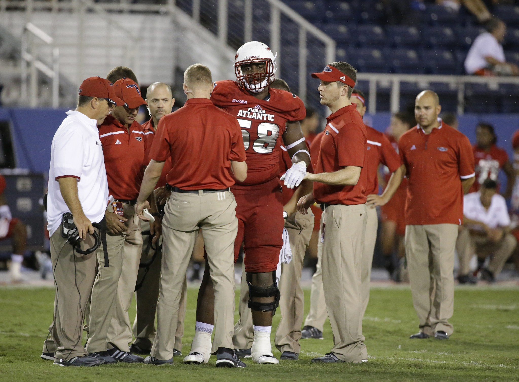 Florida Atlantic offensive lineman Reggie Bain is helped off the field during the second half of an NCAA college football game against Miami, in the early morning hours of, Saturday, Sept. 12, 2015, in Boca Raton, Fla. (AP Photo/Wilfredo Lee)