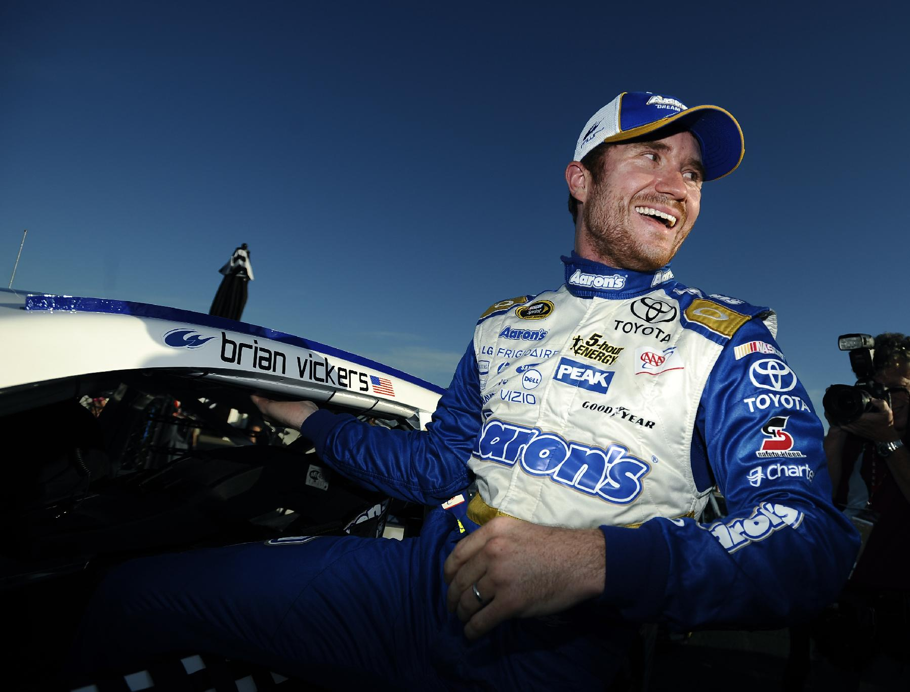 Brian Vickers climbs out of his car after winning the pole for Sunday's NASCAR Sprint Cup Series auto race at Talladega Superspeedway Saturday, Oct. 18, 2014, in Talladega, Ala.   (AP Photo/Rainier Ehrhardt)
